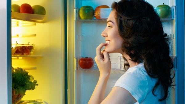 Женщина заглядывает в холодильник с едой